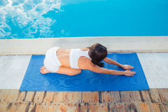 Girl working out on yoga mat outdoors Stock Image
