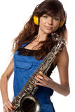 Girl in working overalls with sax Stock Image