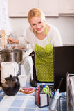Girl working on PC. Blonde girl in apron working on PC at kitchen Stock Images