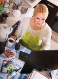 Girl working on PC. Happy blonde girl in apron working on PC at kitchen Royalty Free Stock Photos