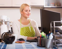 Girl working on PC. Young blonde girl in apron working on PC at kitchen Stock Image