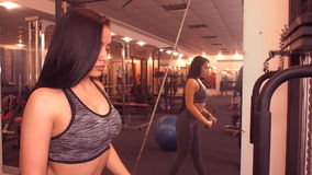 Girl working on the simulator, triceps. Beautiful girl with long hair standing shakes triceps. stock video footage