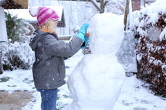 Girl is working on a snowman Stock Photos