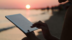 Girl working with tablet PC on beach at sunset. Close-up shot of girl using touch pad sitting on the shore at sunset. Defocused people, sun and sea in background stock footage