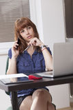 Girl working and talking at the phone. A young woman working on laptop, at desk with a pen and she is talking at the phone Stock Photography