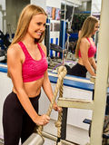 Girl workout on bicep curl machine in sport gym. Royalty Free Stock Photos