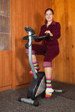 Girl workout on stationary bicycle Royalty Free Stock Photo
