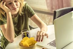 Girl works at a computer and eats fast food. stock photography