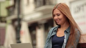 The girl works on a computer on the street and talking on the phone. Close-up. stock footage