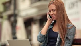 The girl works on a computer on the street and talking on the phone. Young stylish woman with a laptop is sitting on a bench and working. The girl posing in the stock video
