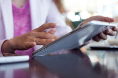 Girl works on the digital tablet, a small depth Royalty Free Stock Photography