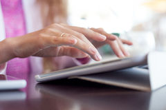 Girl works on the digital tablet, a small depth Royalty Free Stock Images