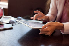 Girl works on the digital tablet, a small depth Royalty Free Stock Photos