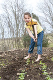 Girl works hoeing garden Royalty Free Stock Images