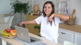 Girl works at laptop, gets good news, rejoices, laughs, looks at camera, slow motion. Young woman use laptop for work from home stock footage