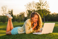 Girl works on the laptop in nature. Royalty Free Stock Photos