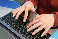 The girl works on a laptop. Two female hands on a black computer keyboard. The concept of the office manager or business woman. Two female hands on a black royalty free stock photography