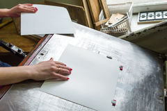 Girl works for paper cutter Stock Photos