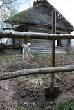 Girl works the soil near an abandoned log cabin, rural Russia. Stock Photography