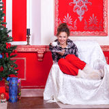 Girl in worm clothes inside a red vintage room with christmas de Royalty Free Stock Photography