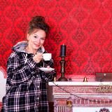 Girl in worm clothes inside a red vintage room with christmas de Royalty Free Stock Photo