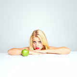 Girl worried by an apple Stock Photography