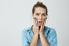 Girl is worried and shocked. Studio portrait of beautiful adult woman with bun hairstyle holding palms on face and. Looking with nervous and troubled expression Stock Photo