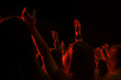 Girl Worshipping at Christian Event. Girl raising her hands with others in the background at a Christian event Stock Photography