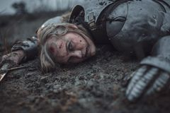 Girl in image of Jeanne d`Arc in armor lies in mud with sword in her hands. Girl with wounds on her face in image of Jeanne d`Arc in armor lies in mud with royalty free stock photo