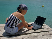 Girl with wrap and laptop on sea Royalty Free Stock Images