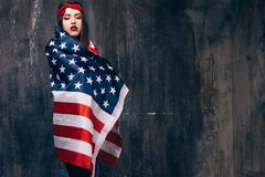 Girl wrapped in american flag on dark background. Patriot, national event celebration, pride, usa citizen concept Royalty Free Stock Images