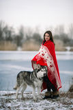 Girl wrapped  in blanket with alaskan malamute dog. Girl with alaskan malamute dog wrapped  in white-red blanket.  They stand over winter lake Stock Photography