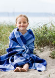 Girl wrapped in blanket at beach stock photos