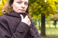 A girl wrapped in a coat to keep warm, the theme of autumn stock photos