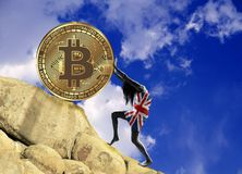 The girl, wrapped in a flag of Great Britain, raises a bitcoin coin up the hill royalty free stock image
