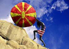 A girl wrapped in a flag of the United States of America, raises a stone to the top in the form of a silhouette of the flag of vector illustration