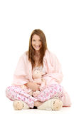 Girl wrapped in pink blanket with toy lamb Stock Photos