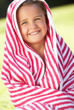 Girl Wrapped In Towel Sitting In Garden Stock Photography