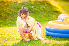 Girl wrapped in towel sitting by the swimming pool Stock Images