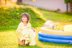 Girl wrapped in towel sitting by the swimming pool Royalty Free Stock Photo