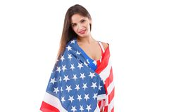 Girl wrapped up in an American flag and looks directly close-up on a white isolated background. A girl in a swimsuit is young, beautiful with a smile wrapped in Royalty Free Stock Image