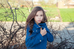 Girl wrapped up in a blue sweater in the wind with tousled hair. From wind and cold Stock Image