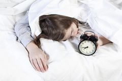 Girl, wrapped in a white blanket, puts out her hand to turn off the alarm. There is eight hours on the alarm clock. Royalty Free Stock Photography
