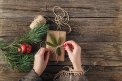 Girl wrapping christmas gift. Woman`s hands holding decorated gi. Ft box on rustic wooden table. Christmas or New year DIY packing. Overhead, flat lay, top view Stock Photography