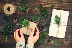 Girl wrapping christmas gift. Woman's hands holding decorated gift box on rustic wooden table. Christmas DIY packing. Girl wrapping christmas gift. Woman's Royalty Free Stock Photography