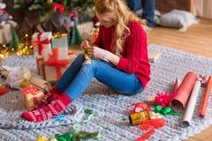 Girl wrapping gift box Stock Photos