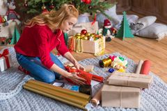 Girl wrapping gift boxes. Blonde girl sitting on grey carpet and wrapping gift boxes at christmastime stock image