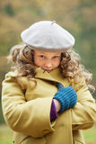 Girl wrapping in winter coat. Blond girl freezing up in a cold autumn day Stock Photos