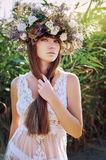 Girl in a wreath. Beautiful girl with long brown hair in ethnic wreath of wildflowers, it is warm autumn colors and a white transparent dress against the Stock Photography