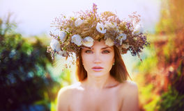 Girl in a wreath. Beautiful girl with long brown hair in ethnic wreath of wildflowers, it is warm autumn colors and a white transparent dress against the Royalty Free Stock Photo